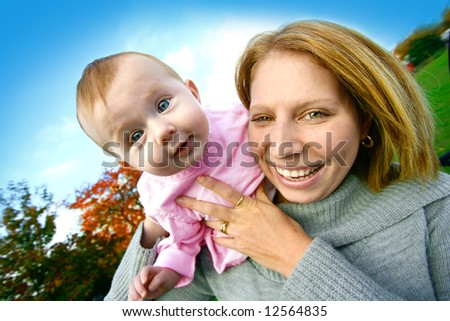 Young mom with her baby girl playing outdoor.