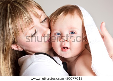 Young mom with her lovely baby son - stock photo
