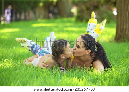 Young mom with her 6 years old child rollerskating in park. Daughter kissing mother. - stock photo