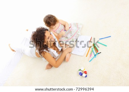 Young mommy playing with her daughter on the floor