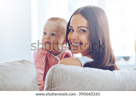 Young mommy. Rear view of cheerful beautiful young woman holding baby girl in her hands and looking at camera with smile while sitting on the couch at home - stock photo