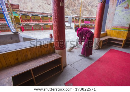 Young monk doing clean inside chapel in temple , Leh India - stock photo
