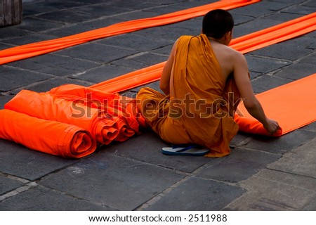 young monk folding robes - stock photo