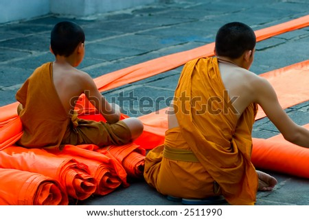 young monks folding robes - stock photo