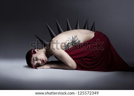 young monster girl sleeping on the floor on dark background - stock photo