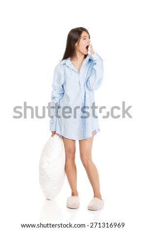 Young morning yawning woman in big shirt and pillow. - stock photo