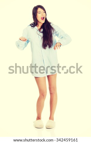 Young morning yawning woman in big shirt and slippers. - stock photo