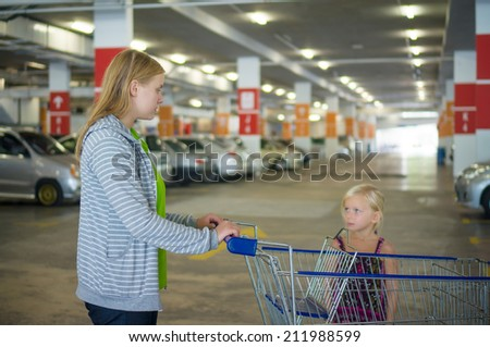 Young mother and adorable daughter in shopping cart on underground car park of supermarket - stock photo