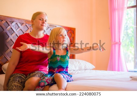 young mother and adorable daughter sit on bed in tropical beach resort room - stock photo