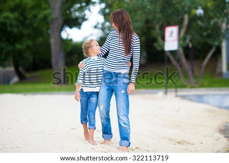 Young mother and adorable little girl enjoying a walk along the lake - stock photo
