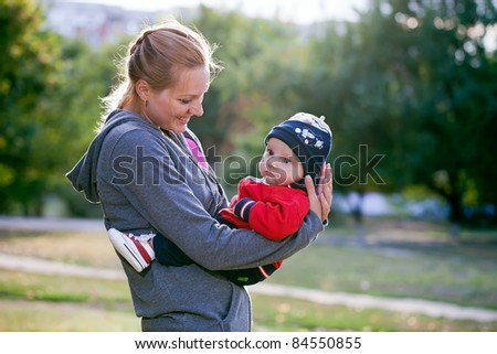 Young mother and at her baby son in park - stock photo