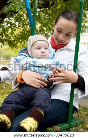 Young mother and baby boy on swing in autumn park - stock photo