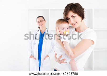 young mother and baby girl in doctor office - stock photo