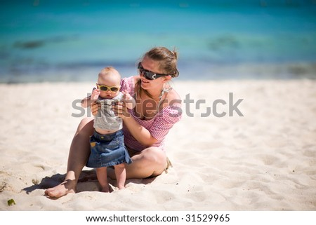Young mother and baby girl in sunglasses on white sand tropical beach - stock photo