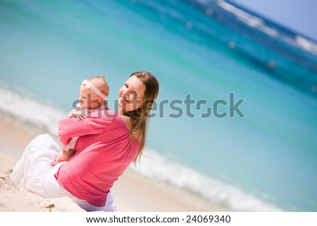 Young mother and baby girl on white sand tropical beach