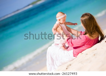 Young mother and baby girl on white sand tropical beach - stock photo