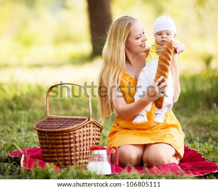 young mother and baby having a picnic outdoor on a warm summer day - stock photo