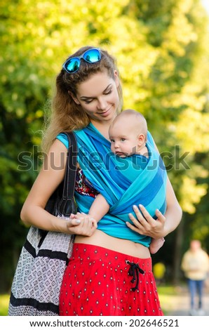 Young mother and baby in a sling. Outdoor. - stock photo