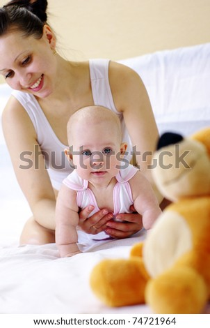 young mother and baby lying on the bed playing with a bear toy
