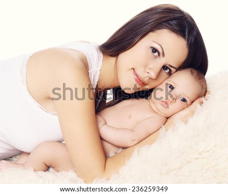 Young mother and baby on the bed at home