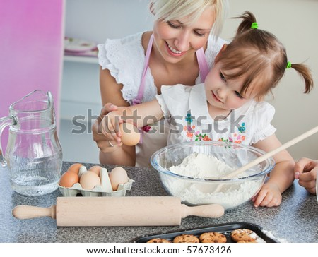 Young mother and child baking cookies in the kitchen