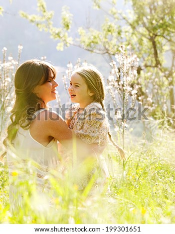 Young mother and child daughter together, hugging and joyfully smiling while relaxing in a field of sunshine and spring flowers while on a summer holiday. Family activities and outdoors lifestyle. - stock photo