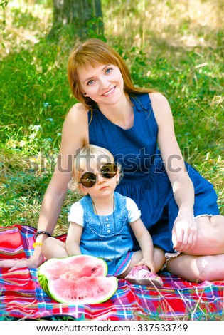 young mother and child sitting in the park and eating watermelon - stock photo