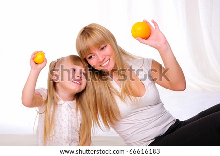 Young mother and child spend time together. kept in the hands of oranges - stock photo