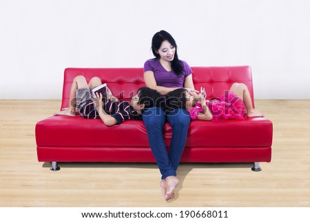 Young mother and children on red sofa at home - stock photo