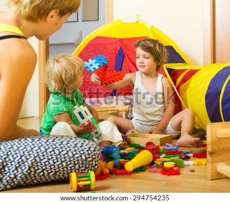 Young mother and children playing with  toys indoor - stock photo