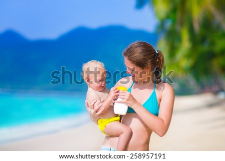 Young mother and cute baby boy enjoying summer vacation in a tropical resort, parent applying sun screen using lotion spray for safe tan and skin care - stock photo