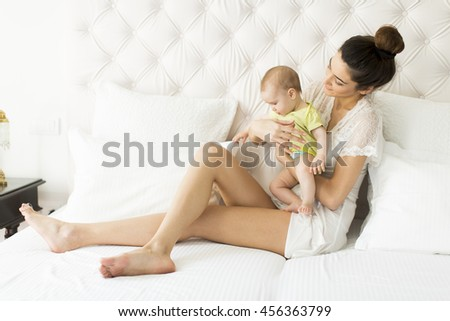 Young mother and cute baby girl on the bed