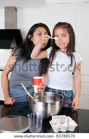 Young mother and cute little daughter cooking together - stock photo