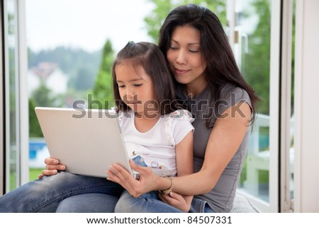 Young mother and daughter at home looking at laptop - stock photo