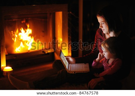 Young mother and daughter by a fireplace with a laptop - stock photo