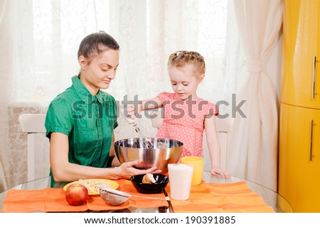 young mother and daughter cooking in the kitchen