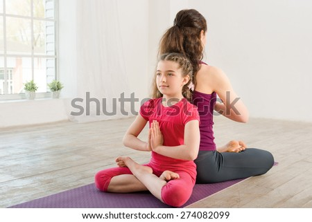 Young mother and daughter doing yoga exercise in fitness studio with big windows on background - stock photo