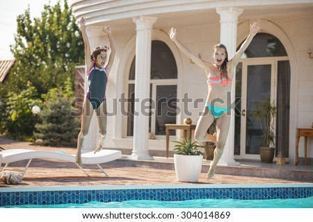 Young mother and daughter jumping into the swimming pool and screaming of joy - stock photo