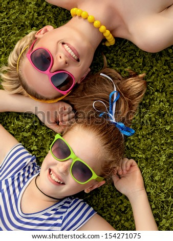 Young Mother and Daughter laying in grass. Colorful Sunglasses - stock photo