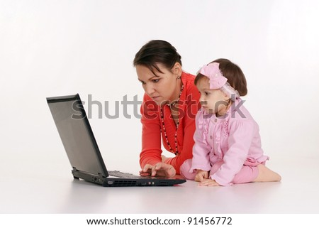 Young mother and daughter  looking at laptop