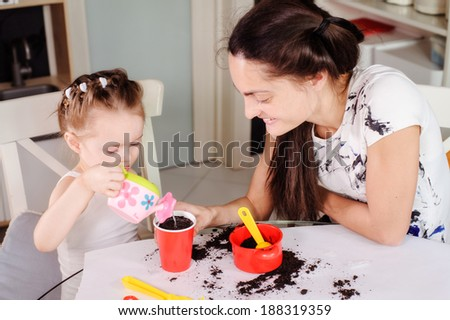young mother and daughter planting a flower at home - stock photo