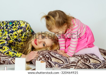 Young mother and daughter playing - stock photo