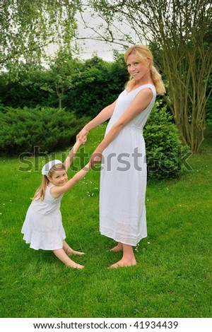 Young mother and daughter playing in meadow - stock photo