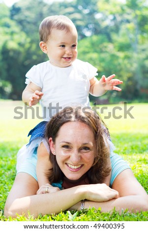 young mother and daughter playing outdoors - stock photo