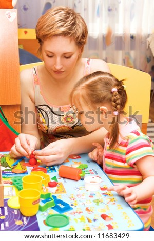 young mother and daughter playing with plasticine in a children's room