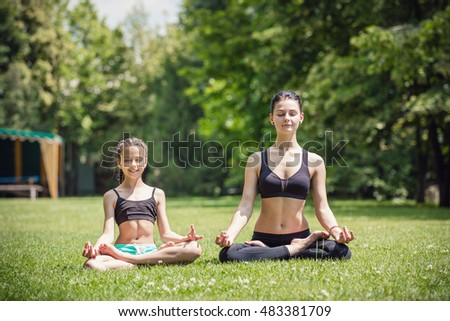 Young mother and daughter practicing in park