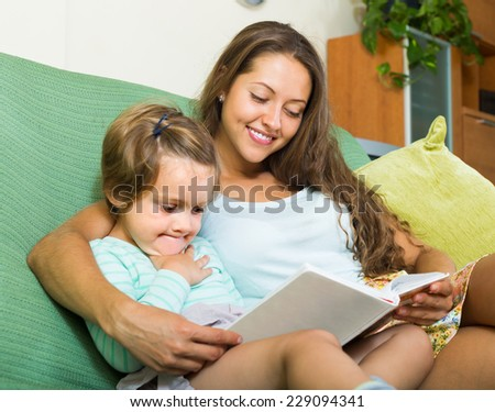 Young mother and daughter reading book on sofa in home - stock photo
