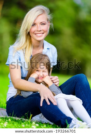 Young mother and daughter sitting on the grass embrace each other. Leisure time of happy family - stock photo