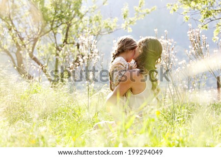 Young mother and daughter together, hugging and cuddling sitting and relaxing in a golden field of sunshine and spring flowers while on a summer holiday. Family activities and outdoors lifestyle. - stock photo