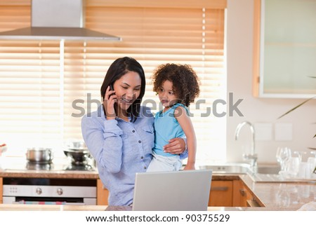 Young mother and daughter using cellphone and laptop in the kitchen together